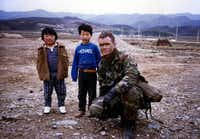 Peter Gudmundsson, as a Marine artillery lieutenant with Korean children during Operation Team Spirit in 1987, says hiring veterans makes good business sense.