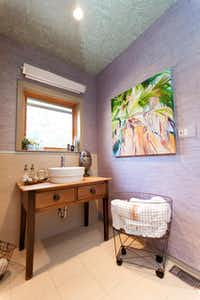 Outfit a guest bathroom with fresh flowers, beautiful hand towels and a few necessities to make their visit comfortable, says designer Abbe Fenimore.(Melanie Johnson Photography)