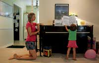 Leigh Isakson watched as her 2-year-old daughter Abby plunks out a tune on the piano at their home in Plano on Wednesday.