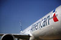 The freshly painted American Airlines 777 bears the new logo and look at Terminal D, where CEO Tom Horton and US Airways CEO Doug Parker announced the merger of the two airlines during a news conference Thursday at Dallas/Fort Worth International Airport.Tom Fox - Staff Photographer