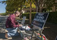 Lee Valerius adds his name to the list of people holding a prayer vigil outside the Southwestern Women's Surgery Center in Dallas on Friday. The clinic will still be able to perform abortions under the state's new restrictions.