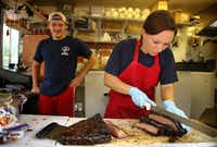 La Barbecue general manager Ali Clem, right,  cuts and serves brisket at the customer window in Austin, the second stop on the Texas BBQ Posse's Austin BBQ Tour.