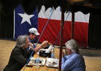 Ken Zarifis of Austin, front left, Evan Butcher of McAllen, back, and Travis Donoho of Austin enjoy lunch under the tent of John Mueller Meat Co.'s trailer restaurant on E. 6th Street in Austin, the Posse's third stop on the Austin BBQ Tour.