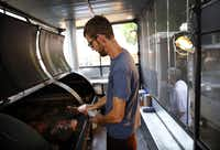 La Barbecue pitmaster John Lewis tends to briskets on his new smoker in Austin.