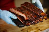 La Barbecue general manager Ali Clem cuts and serves ribs at the customer window of their trailer.