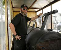 Pitmaster John Mueller poses for a photo with his smoker at John Mueller Meat Co.