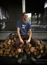 La Barbecue pitmaster John Lewis pops open a beer and takes takes a well earned break atop his oak woodpile in Austin.