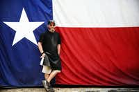 Pitmaster John Mueller poses for a photo in front of his large Texas flag hung from the side of a shipping container at John Mueller Meat Co.