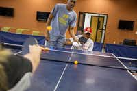 Paralympic table tennis coach Keith Evans helps Quintin Stephens with his backhand stroke while playing against Pam Fontaine, a member of the Paralympic team, during a power wheelchair sports clinic for veterans with disabilities at the UT Arlington Campus in Arlington.( Brittany Sowacke  -  Staff Photographer )