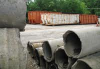 Decades ago, city workers began using the ground above a pumping station for storage of stuff like concrete sewer pipes, wooden guard-rail posts and long industrial bins full of garbage. Eventually, the back side of the lot became a dumping place, with city workers apparently contributing to the junk pile of dirt, used road asphalt, manhole covers and bags of garbage.