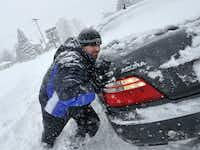 Chad Reams helps a stuck driver along East Market Street in York, Pa. during Saturday's snowstorm on Jan. 23, 2016. (Jason Plotkin/York Daily Record via AP)
