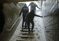 Travelers navigate snow covered steps at the Union Turnpike subway station in the Queens borough of New York during a snowstorm Saturday, Jan. 23, 2016. (AP Photo/Frank Franklin II)