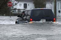 The driver of an SUV looks out of his window on a flooded 10th Ave. in North Wildwood, N.J., at the height of the storm, later backing down the street, Saturday, Jan. 23, 2016. (Dale Gerhard/Press of Atlantic City via AP)