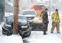 Norwich police and fire personnel respond to a car that slid into a pole Saturday, Jan. 23, 2016, during a snowstorm in Norwich, Conn. (John Shishmanian/The Norwich Bulletin via AP)