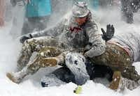 Fallen cadets take a barrage of fire from surrounding Hokies during an annual Civilians vs. Corps of Cadets snowball fight on the Virginia Tech campus in Blacksburg Va., Saturday Jan. 23 2016. (Matt Gentry/The Roanoke Times via AP)