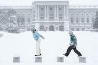 Stephanie Williams and her sister Joely Wilkinson play in the snow in front of the state Capitol in Harrisburg, Pa. on Saturday, Jan. 23, 2016. (James Robinson/PennLive.com via AP)