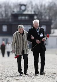 Buchenwald survivors Alexander Bytschok, left, from Ukraine and Andrej Moiseenko from Belarus walk through the former Nazi concentration camp Buchenwald during celebrations marking the 70th anniversary of the liberation of concentration camp Buchenwald near Weimar, Germany Saturday, April 11, 2015. (AP Photo/Markus Schreiber)