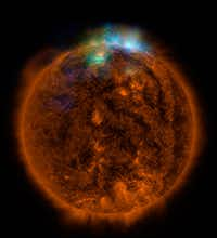 This NASA/JPL-CALTECH handout released December 22, 2014 shows X-rays streaming off the sun in this image showing observations from by NASA's Nuclear Spectroscopic Telescope Array, or NuSTAR, overlaid on a picture taken by NASA's Solar Dynamics Observatory (SDO). This is the first picture of the sun taken by NuSTAR. The NuSTAR data, seen in green and blue, reveal solar high-energy emission. The high-energy X-rays come from gas heated to above 3 million degrees.