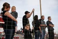 Courtnie Schmidt (left), of Round Mountain, Nevada, holds her daughter, Rilynn Schmidt, 3, while Molly Clark (center bottom), 3, of Tonopah, Nevada, stands on the sideline during a high school football game between Sierra Lutheran and Tonopah in Tonopah Friday August 28, 2015. Tonopah beat the team from Carson City, Nevada 55-26. (Andy Jacobsohn/The Dallas Morning News)
