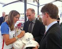 Women's World Cup Champion and two-time Olympic gold medalist Brandi Chastain signs a construction helmet with FC Dallas president Dan Hunt and FC Dallas chairman and CEO Clark Hunt. (Valerie Wigglesworth/The Dallas Morning News)