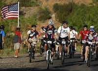Bush (center, in white T-shirt) rode with wounded veterans in the Warrior 100K Ride through Palo Duro Canyon State Park last spring. It combined his love of mountain biking with his efforts to support military service.