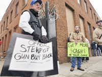 Lawrence Lothrop (left) held a sign for the Stewpot gun buyback event Saturday as a gun activist (right) separately offered to buy guns at the event. Guns collected by Stewpot were to be destroyed, while gun activists wanted to donate them to others.