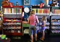 Customers make selections from bins and bins of candy lining the wall at Atomic Candy in Denton.