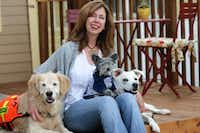 Susannah Charleson, with  Puzzle (the golden), Ollie (on her lap), and Jake Piper.