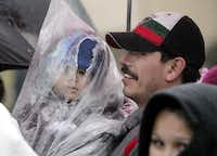 Joaquin Hernandez holds 19-month-old son Jonathan while they wait to enter the 15th Christmas in the Park.