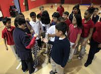 Physical Education teacher Kimberly Rushing hands out jump ropes to fifth-grade students.