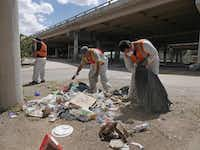 Workers clean up trash under the overpass. The crisis team's task can be grueling and thankless. Many homeless people don't want their help.Ron Baselice  -  Staff Photographer