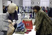 Minnie Jackson (right) checks out clothing donations with volunteer Julie Hagen at Crossroads Community Services in Dallas.