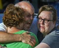 """Tom Sullivan, center, embraces family members outside Gateway High School where he has been searching franticly for his son Alex Sullivan who celebrated his 27th birthday by going to see """"The Dark Knight Rises,"""" movie where a gunman opened fire Friday, July 20, 2012, in Aurora, Colo."""