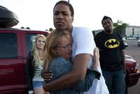 Judy Goos, center left, hugs her daughter's friend, Isaiah Bow, 20, while eyewitnesses Emma Goos, 19, left, and Terrell Wallin, 20, right, gather outside Gateway High School where witnesses were brought for questioning Friday, July 20, 2012, in Aurora, Colo.