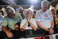 Obama supporters bow their heads during a moment of silence for the victims of the Aurora, Colorado shootings called by US President Barack Obama as speaks on the shootings in Aurora, Colorado at what was scheduled originally as a campaign event at Harborside Event Center July 20, 2012 in Fort Myers, Florida.