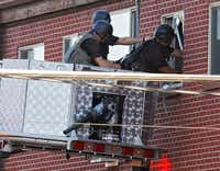 Police use a video camera to look inside an apartment  where the suspect in a shooting at a movie theatre lived in Aurora, Colo., Friday, July 20, 2012. As many as 12 people were killed and 50 injured at a shooting at the Century 16 movie theatre early Friday during the showing of the latest Batman movie.