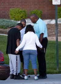 A small group prays outside Gateway High School where witness were brought for questioning Friday, July 20, 2012 in Aurora, Colo.