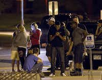 """People use mobile devices as they wait outside Gateway High School where witnesses were brought for questioning after a shooting at a movie theater showing the Batman movie """"The Dark Knight Rises,"""" Friday, July 20, 2012 in Aurora, Colo."""