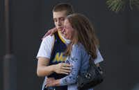 Eyewitness Jacob Stevens, 18, hugs his mother Tammi Stevens after being interview by police outside Gateway High School where witnesses were brought for questioning Friday, July 20, 2012 in Aurora, Colo.