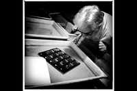 Robert Messina inspects a contact sheet in a tray of fixer after the lights are back on in the printing room at The Color Lab, Dallas, Texas.