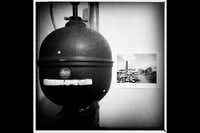 A vintage Leitz enlarger head and an old print tacked to the wall in the printing room.