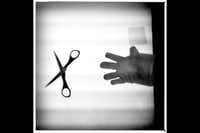 Scissors and a cotton glove sit on a light table.