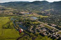 A balloon floats above Steamboat Springs.  Onboard, passengers gaze down on the city and slopes while drifting silently with the currents.
