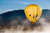 A hot air balloon drifts near the ground in Steamboat Springs.  Because there is no steering on a balloon, pilots are at the mercy of air currents to determine direction.