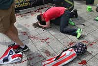 A man tries to comfort a victim near the scene of the first explosion near the finish line of the Boston Marathon.(John Tlumacki - The Boston Globe)