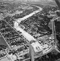 An aerial photo shot during the construction of Interstate 35E in 1961 graphically captured how the project gashed the community in two. Now plans for a deck park similar to Klyde Warren Park in downtown Dallas has some wondering if some of the damage can be undone.(File Photo -  Staff  )