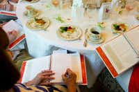 """Ellen Welch takes notes in """"Food for Thought"""" after the monthly potluck meeting of her cookbook club in Dallas on Tuesday, April 16, 2013. The members choose a cookbook and each month they do a potluck of recipes from the book, then they critique them and tweak them."""
