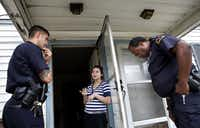 Officers Brandon Byrd (left) and Rory Jones (right) listen to Gabriela Popoca after responding to a call about a verbal dispute between neighbors while on patrol South Dallas on March 4. Flat population over the decade means the city has reached a long-sought goal of having three officers per thousand. The likelihood now exists that the city will choose to hire no new police officers even to replace those who leave.