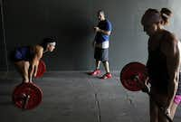Audra LeBeau (left) and Julianne Kennedy (right) of the CrossFit Dallas Central team did dead lifts as coach Noah Rothman watched the clock recently.