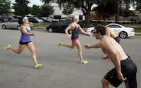 Audra LeBeau (far left) gets ready to tag Trey Kubacak (bottom right) as Julianne Kennedy gets ready to tag Don Walker during a 100 meter sprint relay at CrossFit Gym. LeBeau, Kubacak, Kennedy and Walker are all part of the CrossFit Dallas Central team training for an upcoming national competition.